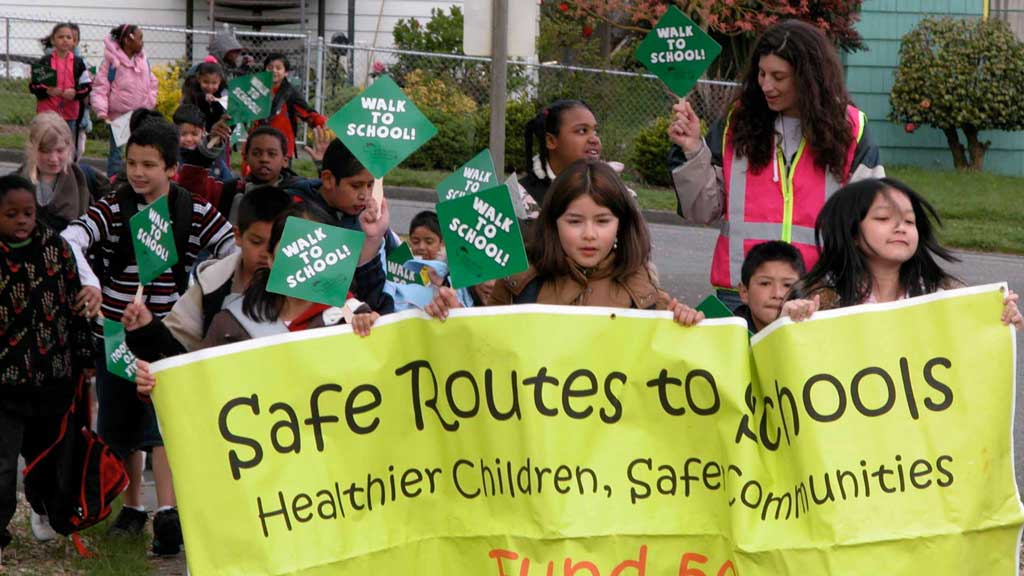 Children holding safe routes to school signs
