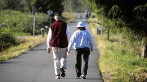 an elderly couple walking on a trail
