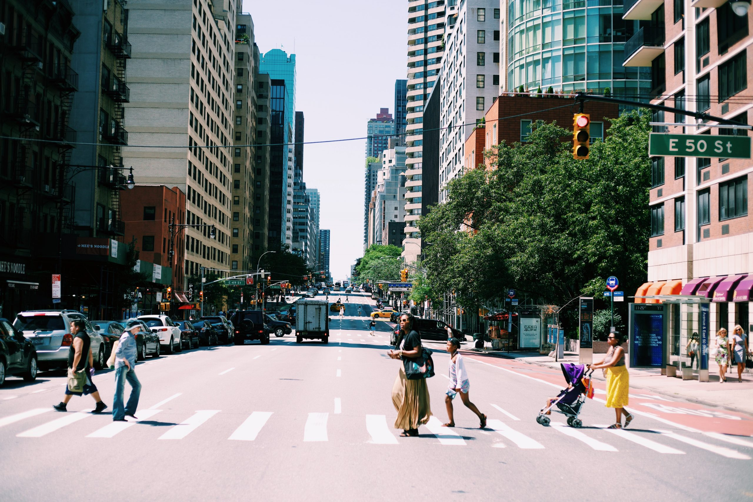 People cross the street in a crosswalk in a downtown area with tall buildings